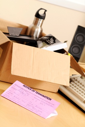 A box with personal affects and a pink slip sitting on a desk