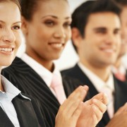 A row of people in professional attire smiling and clapping