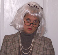 A woman in a gray wig with a pair of glasses on her face and another on her head