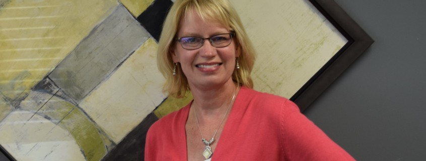 A smiling blond woman with glasses