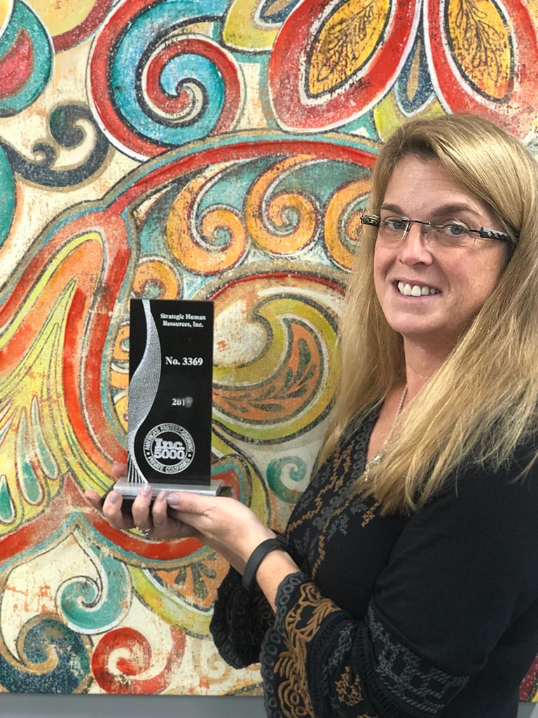 strategic HR inc. president, Robin Throckmorton, holding the Inc 5000 Award recognizing strategic HR inc. as one of the fastest growing companies in America!