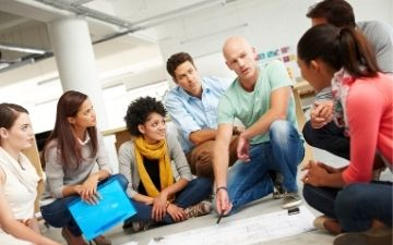 Photo of a team discussion with team members seated on the ground forming a circle, representing Employee Relations