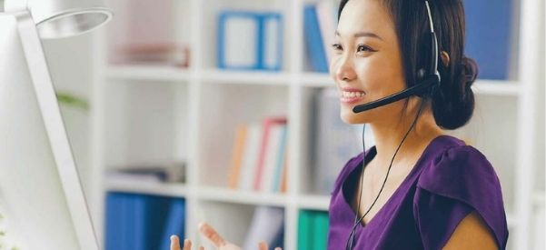 Photo of woman talking on a headset while at her computer, representing our Virtual HR Solutions.
