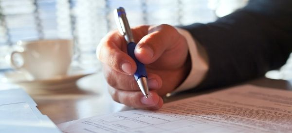 Photo of a man's hand holding a pen reviewing a legal document, representing Legal Compliance & Recordkeeping Services