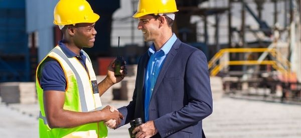 Photo of two men wearing hard hats working at a construction site, representing Health, Safety & Security