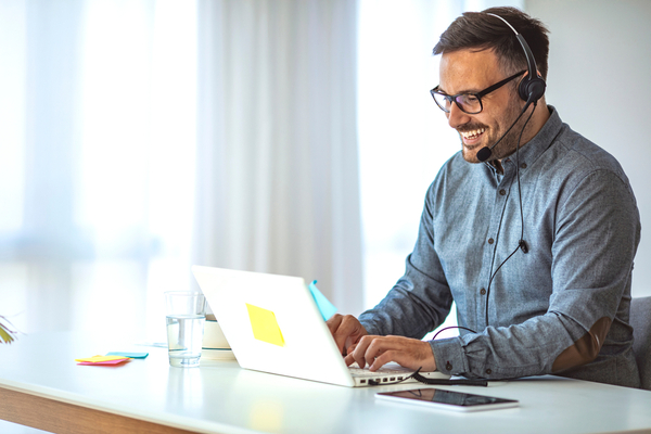 Photo of HR Contractor working remotely on his laptop while wearing a headset