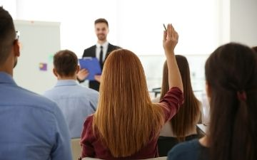 Photo of woman raising her hand to ask a question at a training session, representing Training & Development Services